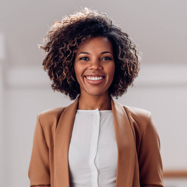 Portrait of young cheerful african american woman Portrait of young cheerful african american woman wearing brown suit smiling and looking at camera african american ethnicity stock pictures, royalty-free photos & images