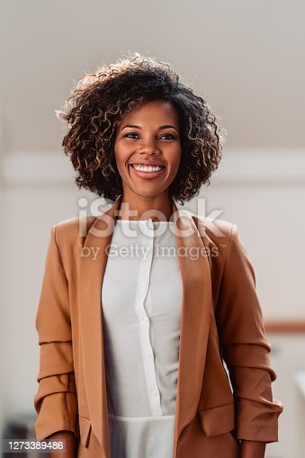 Portrait of young cheerful african american woman wearing brown suit smiling and looking at camera