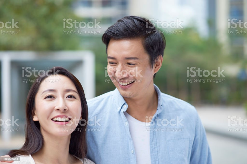 portrait of young Chinese couple standing & smiling outdoor stock photo