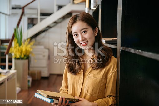 Close-up of smiling Chinese businesswoman in mid 20s standing next to book case within small office in Shanghai.