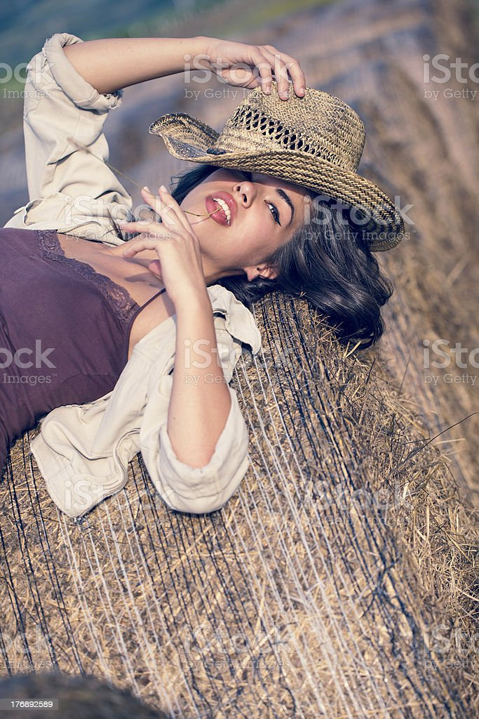 Portrait Of Young Country Girl Lying On Hay Bales stock photo