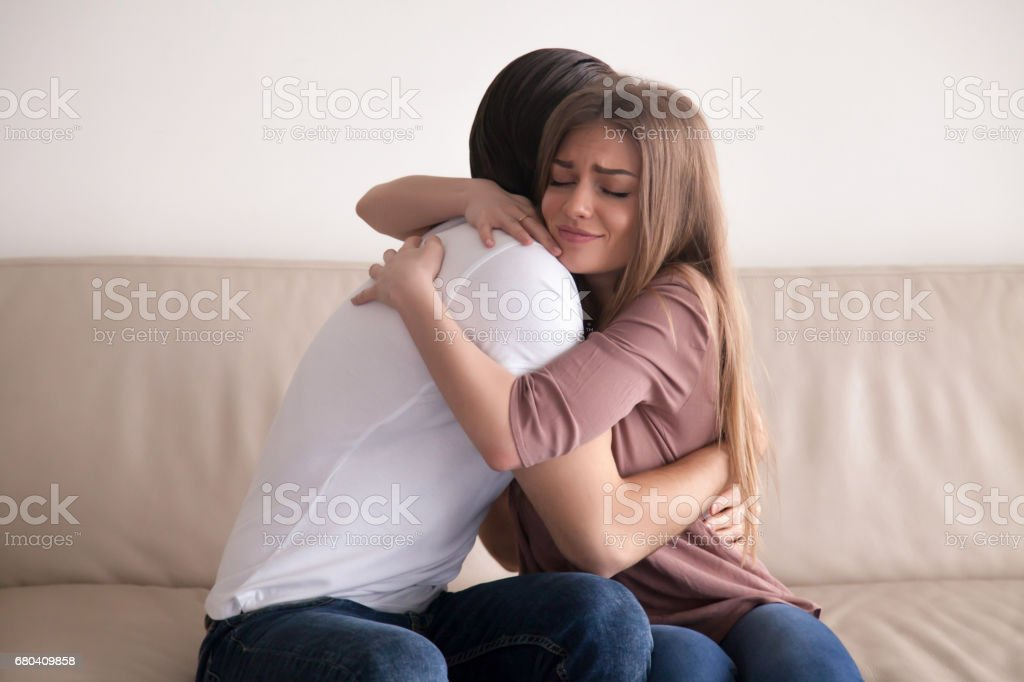 Portrait of young couple hugging tight sitting on couch indoors stock photo