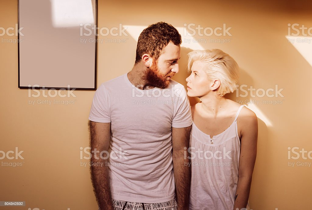 Portrait of young couple in living room looking each other. Portrait of young couple, standing by the wall in living room. Picture frame on the wall. 2015 Stock Photo