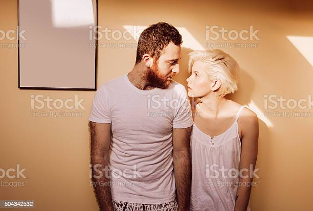 Portrait Of Young Couple In Living Room Looking Each Other Stock Photo - Download Image Now