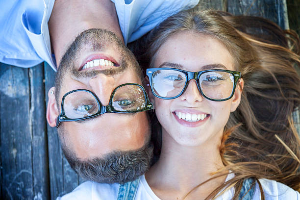portrait of young couple lying on wooden bench stock photo