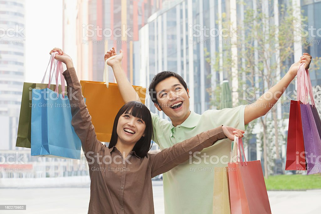 Portrait of young couple posing with shopping bags in hands royalty-free stock photo