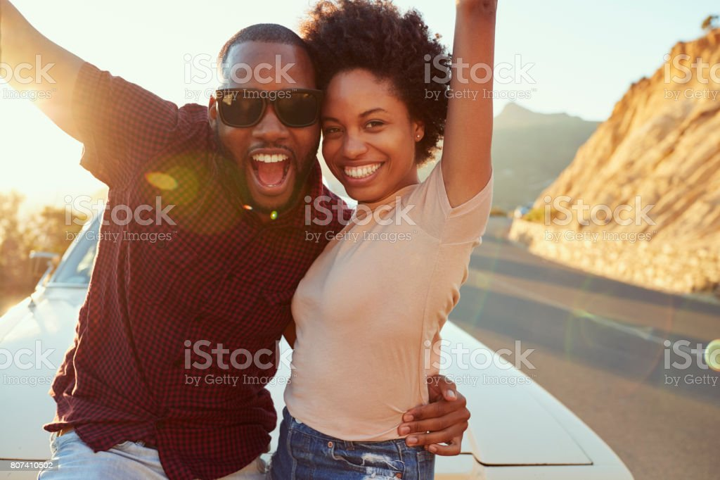 Portrait Of Young Couple Standing Next To Classic Car stock photo