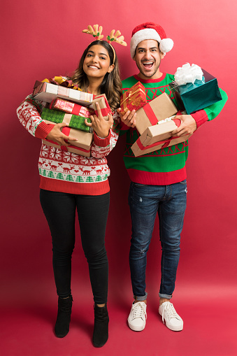 Full length of happy boyfriend and girlfriend holding gifts isolated in studio