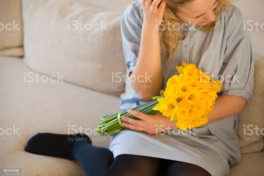 Portrait of young curly hair woman with yellow daffodils. Girl sitting on  the sofa and holding bouquet indoors. Woman in blue dress and beautiful  bunch of ... 694f1eff0