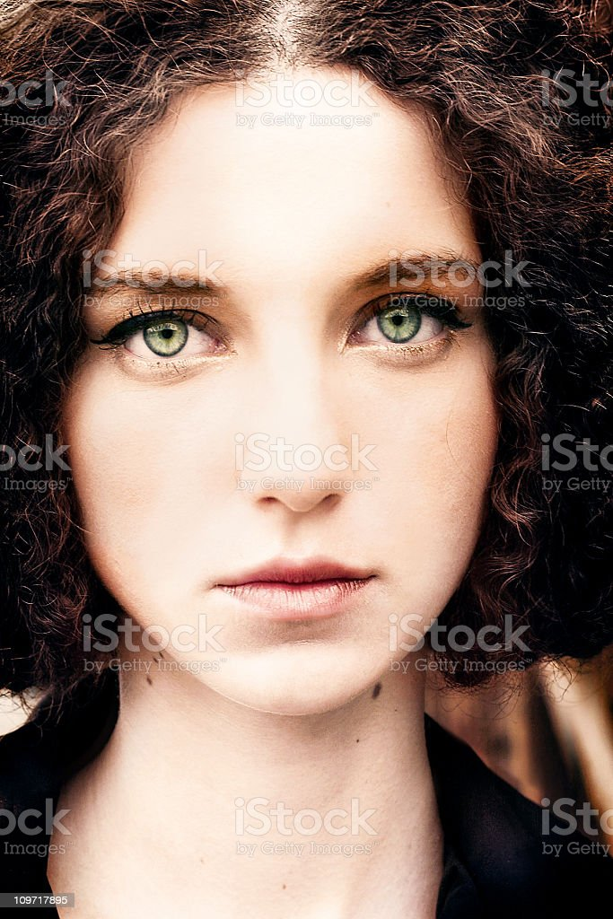 Portrait of Young Curly Haired Woman with Large Green Eyes royalty-free stock photo
