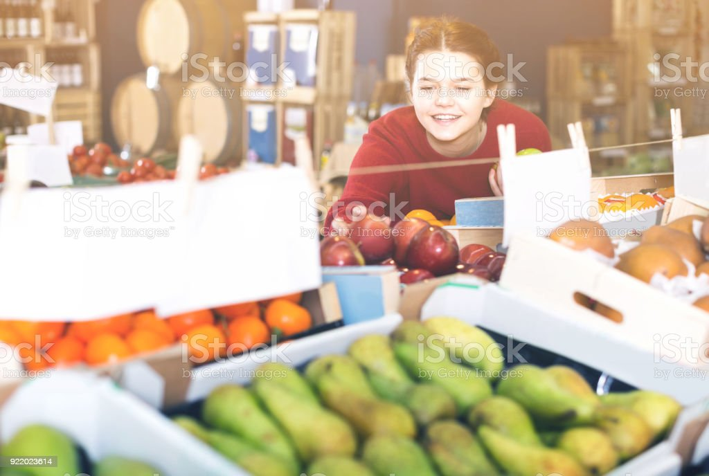 Portrait of  young customer selecting apple in grocery stock photo