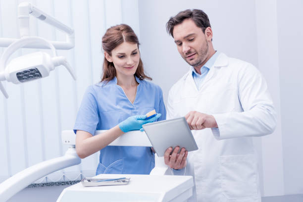 porträtt av ung tandläkare diskuterar arbetet tillsammans och använda surfplatta i tandvårdsklinik - two dentists talking bildbanksfoton och bilder