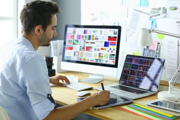Porträt der jungen Designer sitzen an Grafikstudio vor Laptop und Computer während der Arbeit online. – Foto
