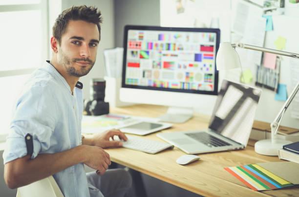 porträt der jungen designer sitzen an grafikstudio vor laptop und computer während der arbeit online - nachrichten video stock-fotos und bilder