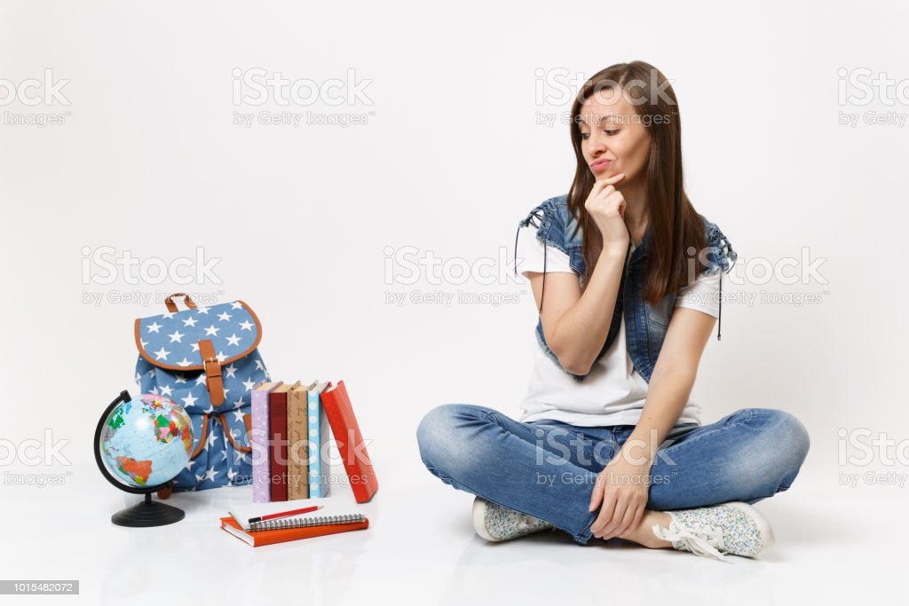 Portrait of young disgusted dissatisfied woman student keeping hand near face sitting looking on globe backpack, school books isolated on white background. Education in high school university college. stock photo
