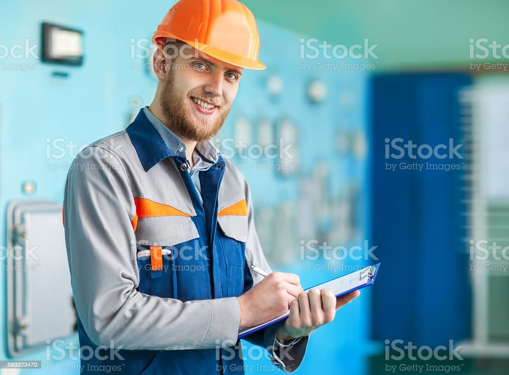 Portrait of young engineer taking notes at control room stock photo