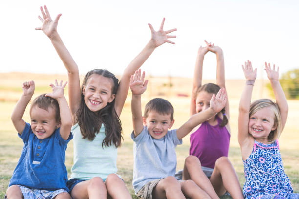 porträt des jungen ethnischen geschwister außerhalb - sommerfest kindergarten stock-fotos und bilder
