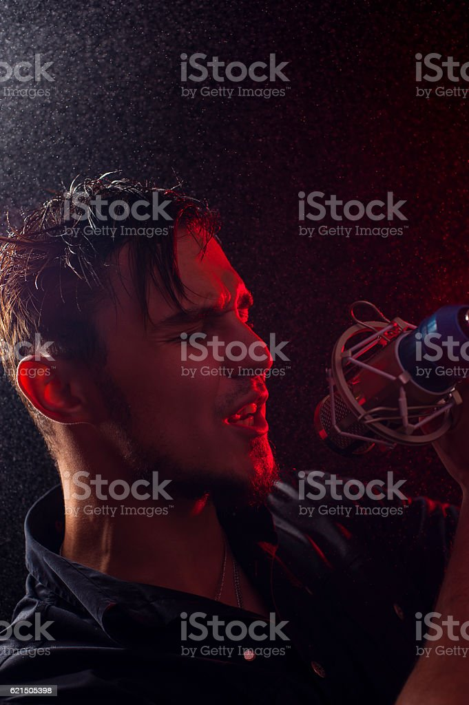Portrait of young expressive rock singer with mic foto stock royalty-free