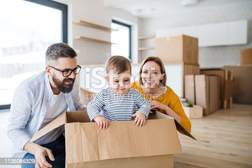 istock A portrait of young family with a toddler girl moving in new home. 1135086329