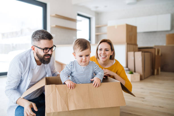 a portrait of young family with a toddler girl moving in new home. - house hunting stock photos and pictures