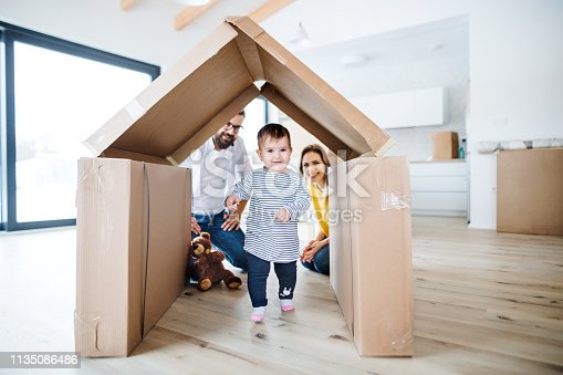 istock A portrait of young family with a toddler girl moving in new home. 1135086486