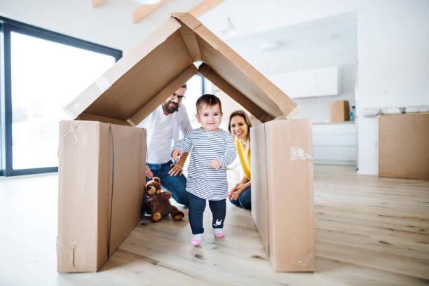 un retrato de la familia joven con una muchacha del niño que se mueve en nuevo hogar. - nuevo bebé fotografías e imágenes de stock