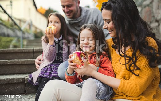 A portrait of young family with two small children in town in autumn, eating apples.