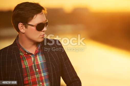 907934274 istock photo Portrait of young fashion man in sunglasses at sunset 469291908