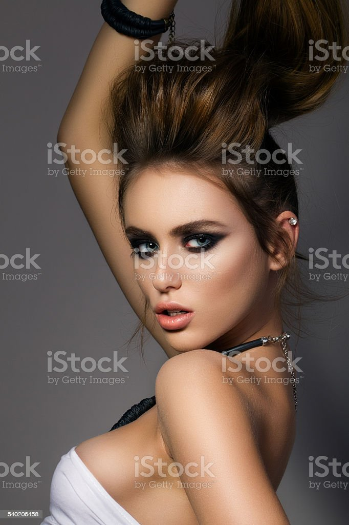 Portrait of young fashion model holding her pony tail stock photo