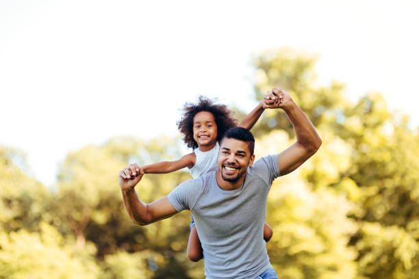 retrato del joven padre llevando a su hija en la espalda - hija fotografías e imágenes de stock