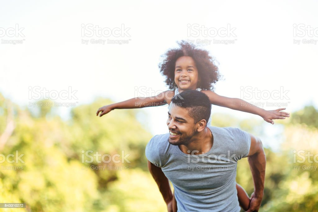 Portrait of young father carrying his daughter on his back stock photo