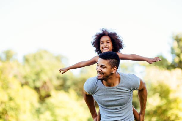 portrait of young father carrying his daughter on his back - fofo descrição física imagens e fotografias de stock