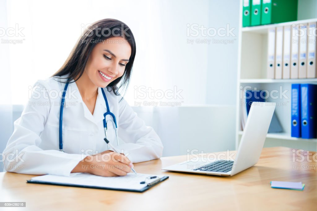Portrait of young female doctor writing conclusion of test stock photo