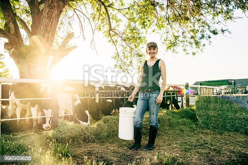 Backlit by sun, she is holding bucket of feed for young calves.
