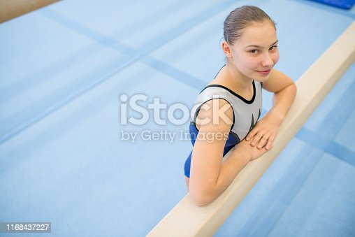 Portrait Of Young Female Gymnast Chalking Her Grips