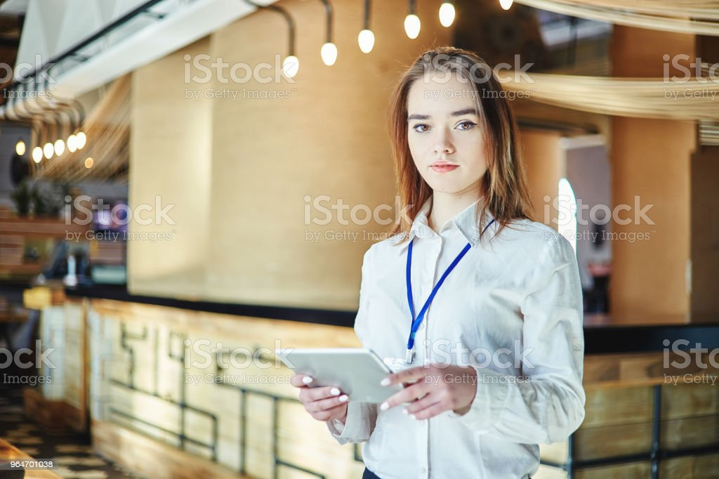Portrait of young female manager looking at camera with tablet computer in her hands and badge around her neck royalty-free stock photo