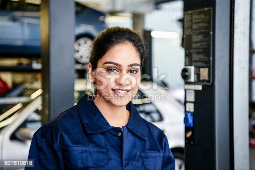 istock Portrait of young female mechanic in garage 827810818