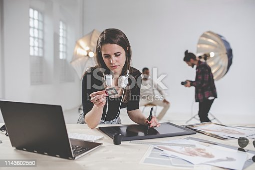 Portrait of young female photographer in photography studio