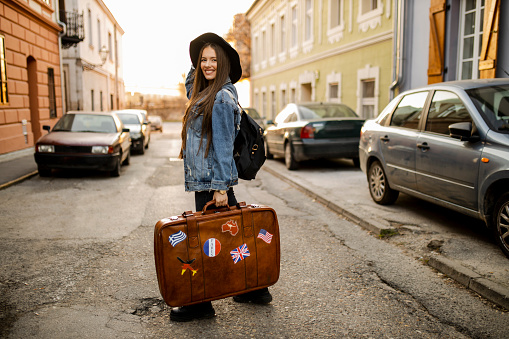 Portrait of young female tourist with retro suitcase