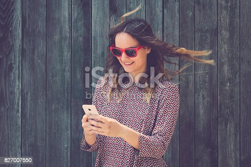 istock Portrait of young female using smartphone against wooden wall 827007550