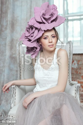 spring concept girl with big flower sitting in armchair