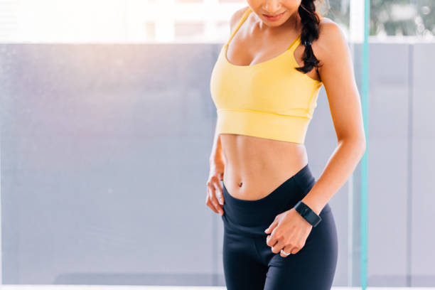 Porträt des jungen Fit Frau im Fitness-Studio, die Hände auf den Hüften Pose. Fitness weibliches Modellbild – Foto