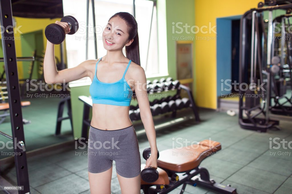 Portrait Of Young Fitness Woman Workout With Dumbbell Stock