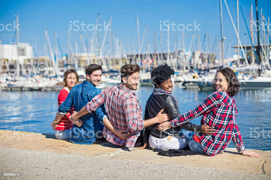 Portrait of young friends sitting at harbor foto de stock royalty-free