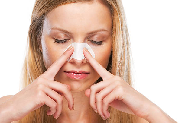 portrait of young girl applying clear-up strips on nose stock photo