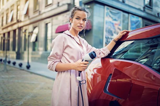 portrait of young girl charging her electric car in the city - auto a combustibile alternativo foto e immagini stock