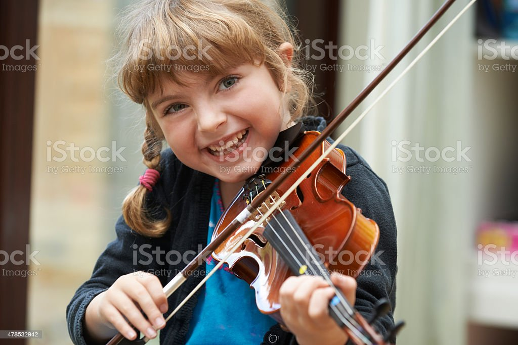 Portrait Of Young Girl Learning To Play Violin stock photo