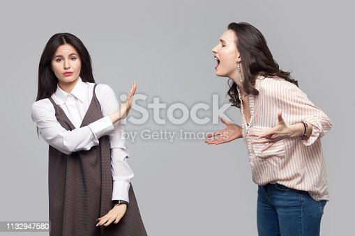 istock Portrait of young girl looking at camera and showing stop or ignore to another girl who screaming at her. conflict between two friend or partners. 1132947580