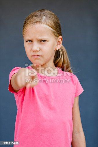 istock Portrait of young girl pointing finger at the camera 838095404