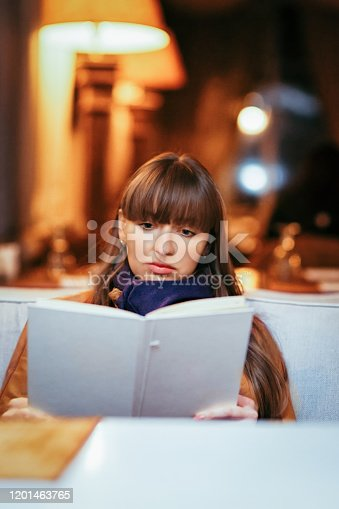 Portrait of a young girl reading menu in a restaurant.